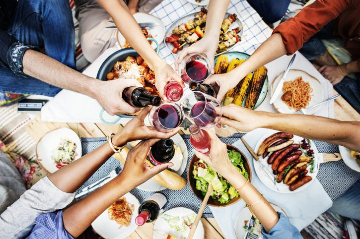 seven people clinking glasses of red wine or beer bottle over a barbeque picnic table